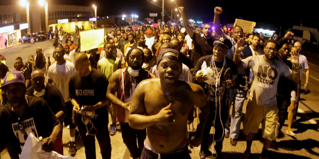 People march Tuesday, Aug. 19, 2014, during a rally for Michael Brown, who was killed by police Aug. 9 in Ferguson, Mo. Brown's shooting has sparked a more than week of protests, riots and looting in the St. Louis suburb. (AP Photo/Charlie Riedel)