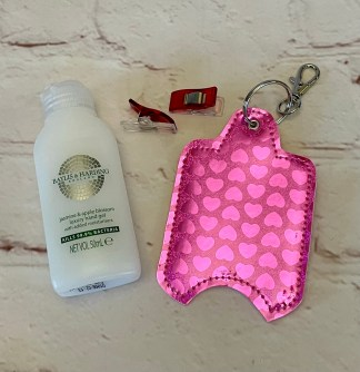 Picture of a bright metallic shiny pink hearts hand sanitiser case