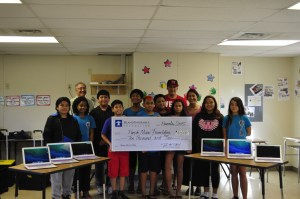 After-school students at Kamaile Academy pose with a check from Island Insurance Foundation that helped us buy a fleet of macbook airs that are used in classes and workshops.