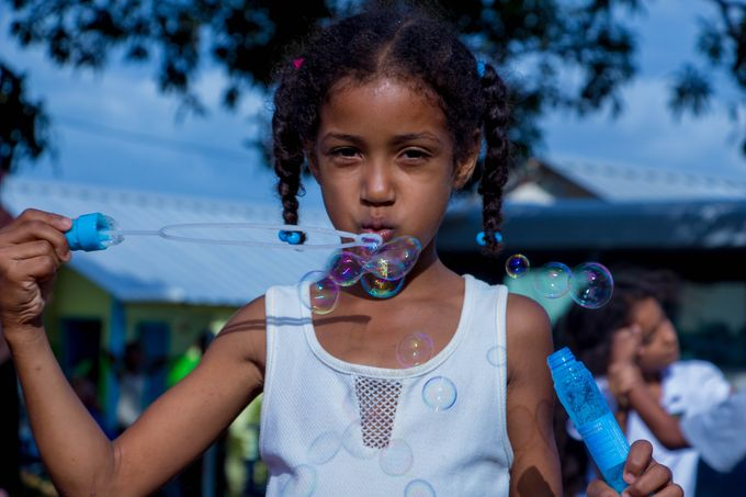 girl wearing a white tank top, blowing bubbles