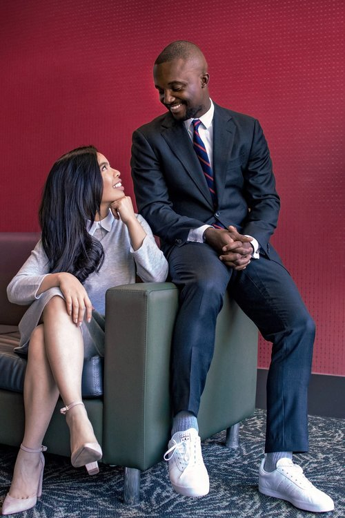 woman sitting on gray leather sofa beside a man while looking each other