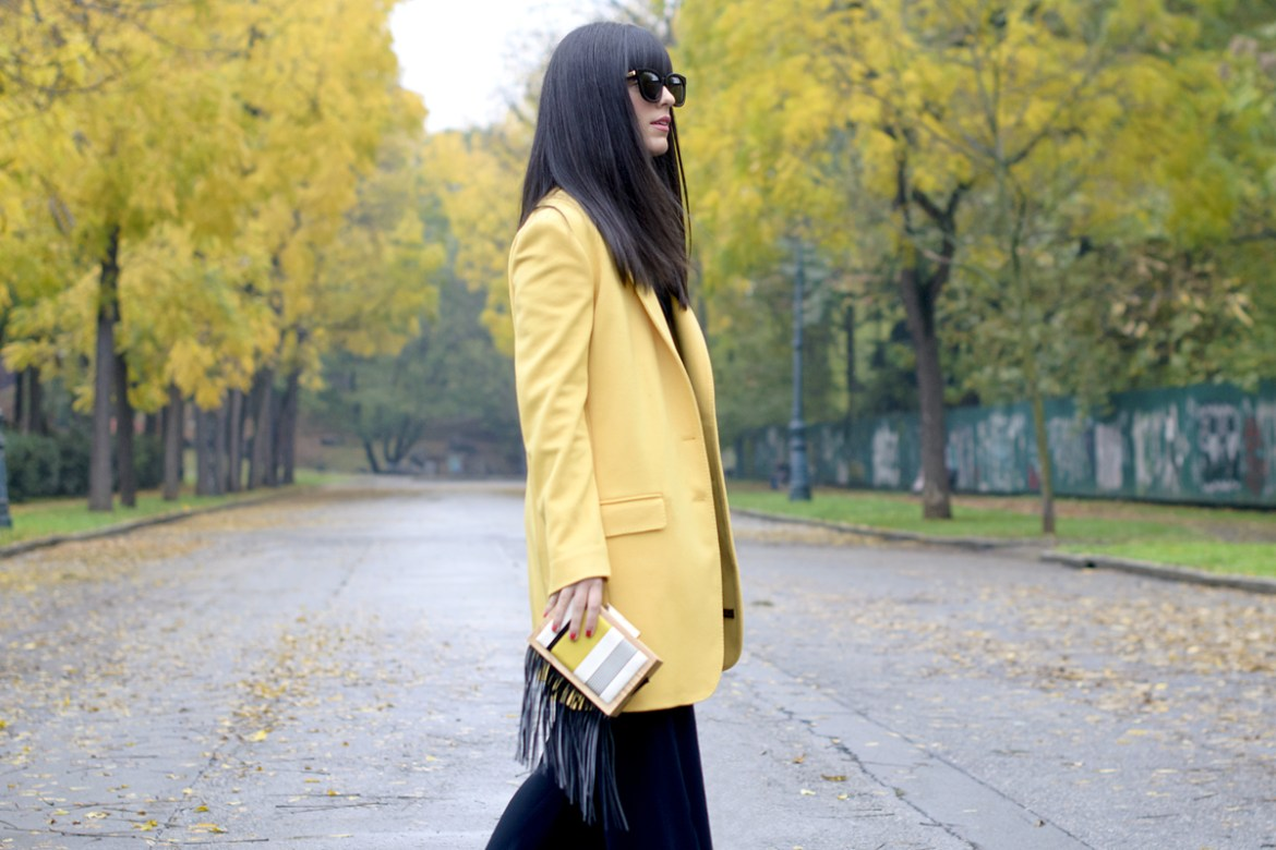 Cappotto giallo su un look total black