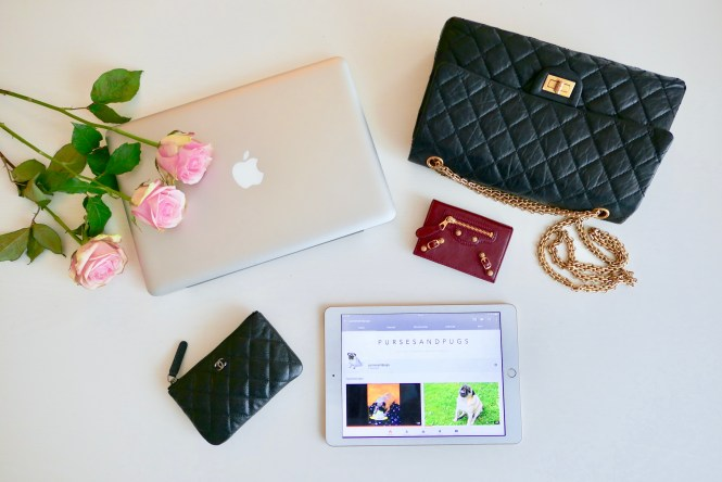 Flat lay of my MacBook Pro, iPad, black Chanel Reissue 226 bag, black Chanel small O case, burgundy Balenciaga card holder, pursesandpugs YouTube channel, roses