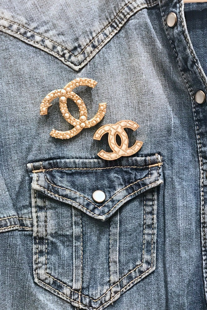 Chanel brooches on a denim shirt.