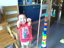 Nih anak bangga berhasil bikin menara tinggi, dibantu bapaknya sih bagian pondasinya. Tuh bapaknya ngukur tinggi menaranya
