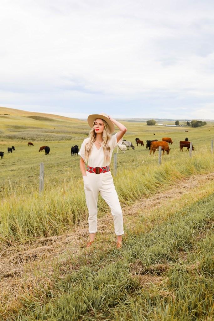 Smash + Tess Romper Styling with felt fedora, beaded belt. Boho western style. Aria Romper in Winter Cream. Cattle field in Alberta.