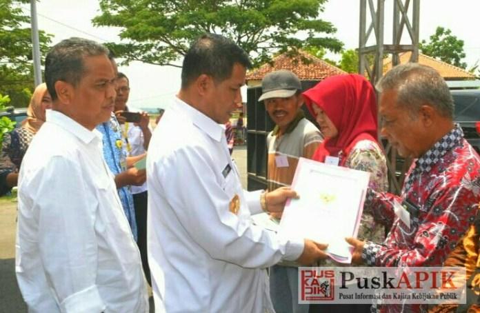 Bupati Junaedi menyerahkan sertifikat tanah ke warga (foto : red)