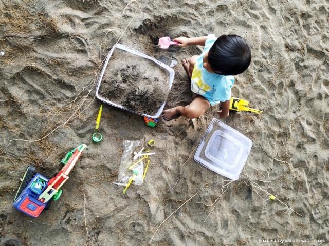 Setelah basah lepek raka ganti baju dan lanjut main pasir