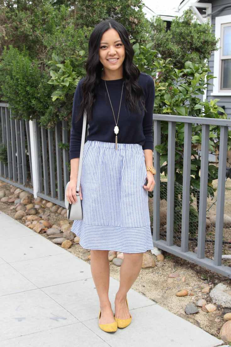 Striped skirt + navy sweater + Long necklace + Grey bag + Yellow flats