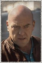 """Dean Norris como James """"Big Jim"""" Rennie. Político e dono de uma loja de carros usados."""
