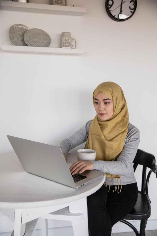 muslim female freelancer typing on laptop during coffee break