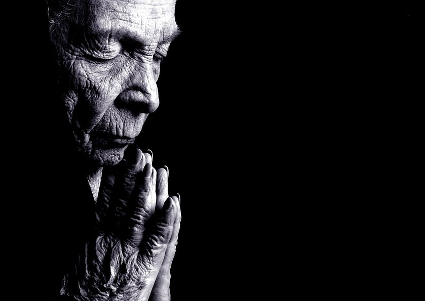 Portrait on Black Of Old woman Praying