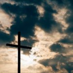 cross with sun and clouds