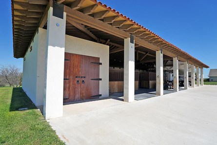 A three sided concrete horse barn 112×50 with 6 concrete stalls (4-17×17 & 2-12×12), a large tack room, with a Mexican tile roof.