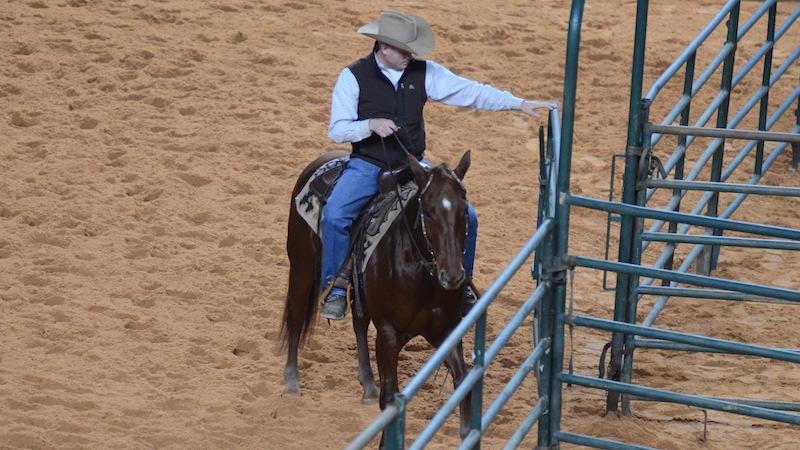 man on horse closing gate