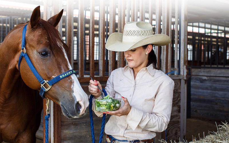 Ashley Davis demonstrating eating nutritious foods while with her horse