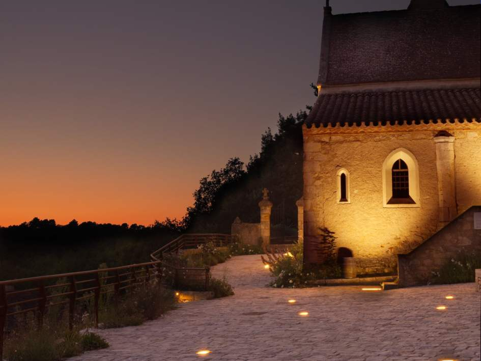 coucher de soleil a bonaguil avec chapelle éclairée en premier plan