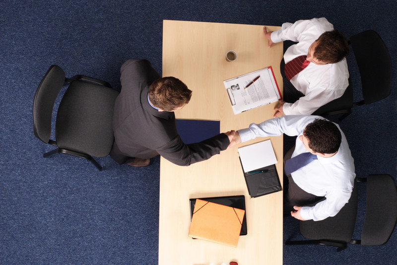 Team of Lawyers shaking hands over a meeting table