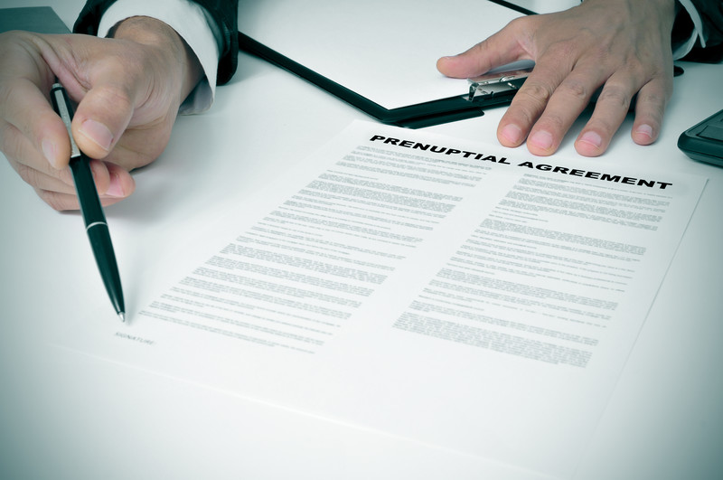 Lawyer pointing where to sign on Prenuptial agreement
