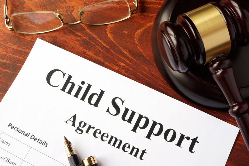 Gavel and eye classes on a table, with a child support agreement waiting to be signed