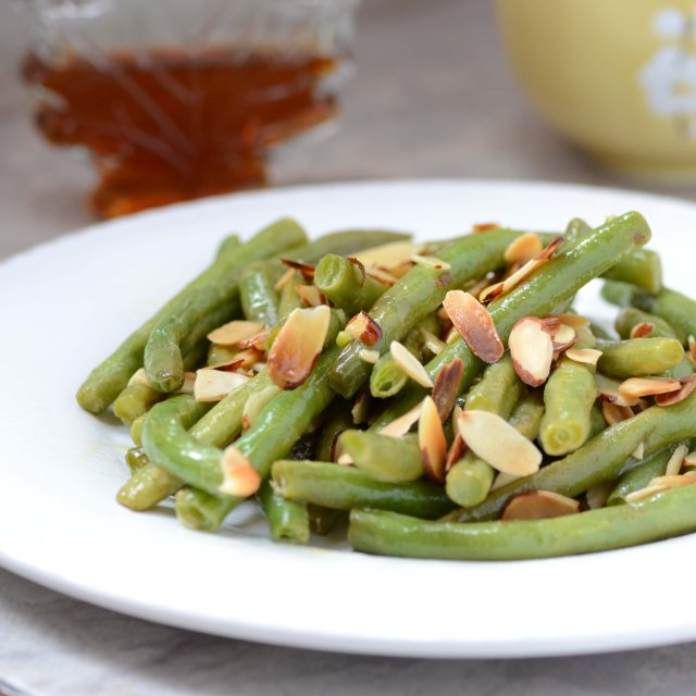 A delicious maple mustard marinade makes a subtle, sweet, and savory coating for roasted green beans that are topped with toasted almonds. | QueenofMyKitchen.com