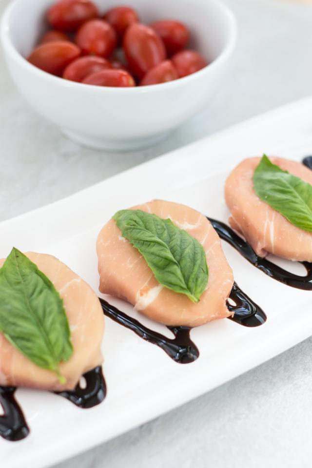 Prosciutto Wrapped Mozzarella with Basil – An easy and elegant appetizer you can assemble in under 5 minutes! Perfect on top of bread or tomato slices and a great addition to antipasto platters. | QueenofMyKitchen.com