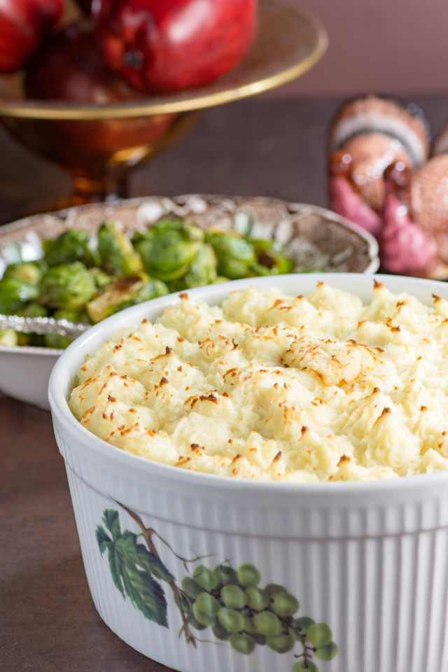 Make Ahead Roasted Garlic Mashed Potatoes - A classic side dish that feeds a crowd and can be made entirely ahead of time. Great for holiday entertaining. #thanksgiving #thanksgivingside #thanksgivingsides #holidayfood #mashedpotatoes
