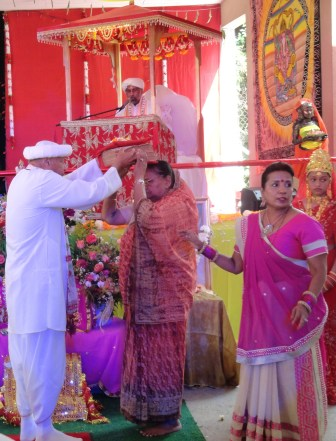Pandit Rishi Misir placing the Ramacaritamanasa on the head of Devi Mata