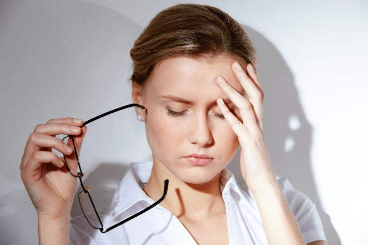 A woman closes her eyes and touches her forehead while suffering from a headache