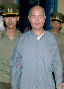 """Hai Công an dẫn HT Thích Quảng Độ ra trước Toà án Nhân Dân Tp Hồ Chì Minh tháng 8 năm 1995 xử tội """"đi cứu trợ nạn nhân lũ lụt ở đồng bằng Sông Cửu Long""""."""
