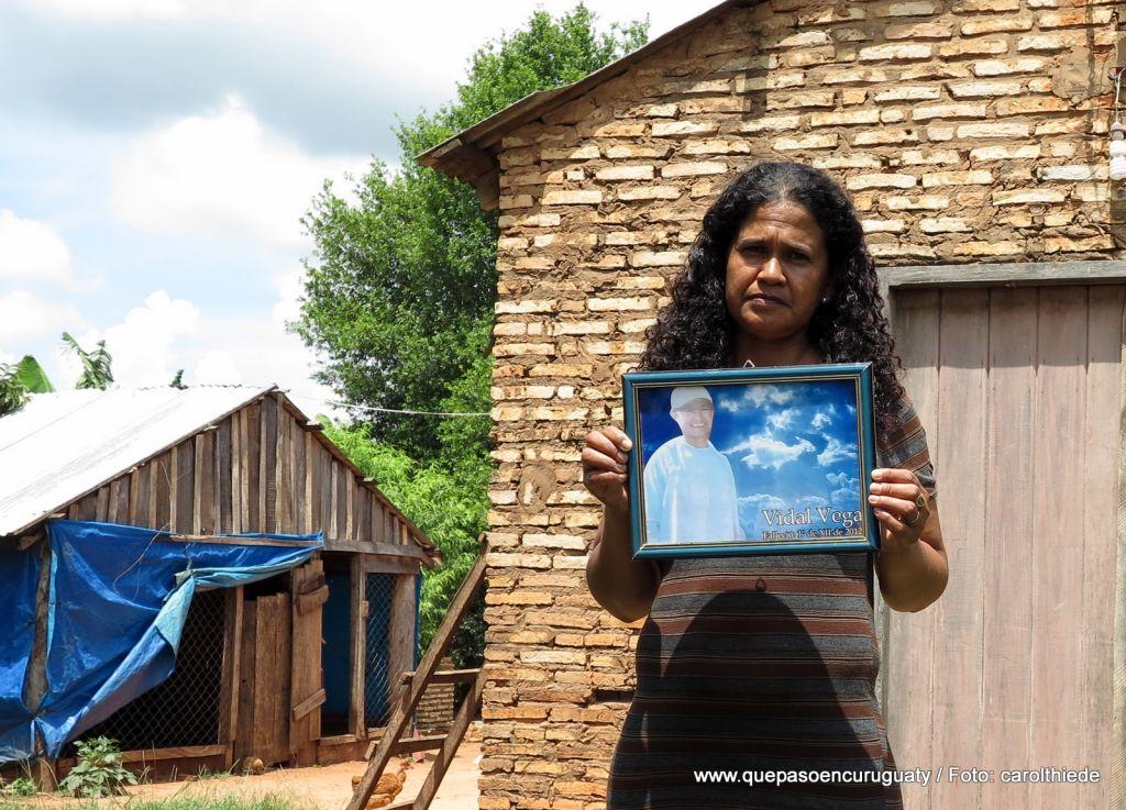 La pareja del dirigente campesino Vidal Vega, asesinado en diciembre de 2012 durante la investigación del caso, frente a la casa que compartían. 15 de diciembre de 2013, Marina kue, Curuguaty.