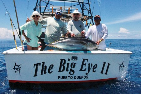 4 men with a tuna on a boat