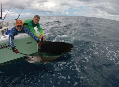 man holding sailfish