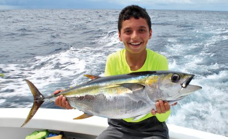 Boy holding a tuna