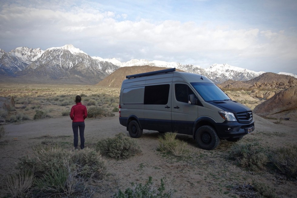 Woman staring at majestic mountains with Sprinter van