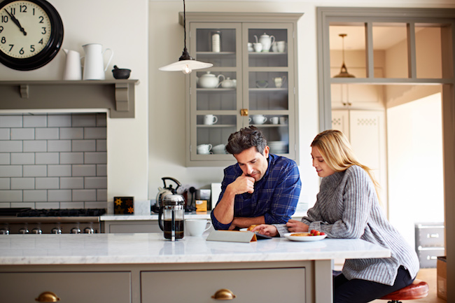 Shot of a young couple using a digital tablet while sitting at their kitchen table at home