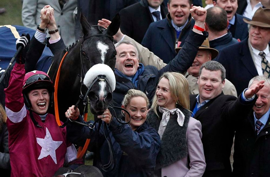 (FILES) In this file photo taken on March 18, 2016, Jockey Bryan Cooper (L) celebrates with horse Don Cossack and connections including trainer Gordon Elliott (2nd R) and owner Michael O'Leary (C) in the winner's enclosure after his victory in the Cheltenham Gold Cup on the final day of the Cheltenham Festival horse racing meeting at Cheltenham Racecourse in Gloucestershire, south-west England. - Leading Irish trainer Gordon Elliott's apology for being photographed talking on the phone while sitting on a dead horse has fallen on deaf ears, with English owners Cheveley Park Stud removing their horses from his charge on March 2, 2021. Elliott may have lost Cheveley Park Stud and their eight horses but his principal owner, Ryanair boss Michael O'Leary's Gigginstown House Stud, is standing by him. (Photo by Adrian DENNIS / AFP)