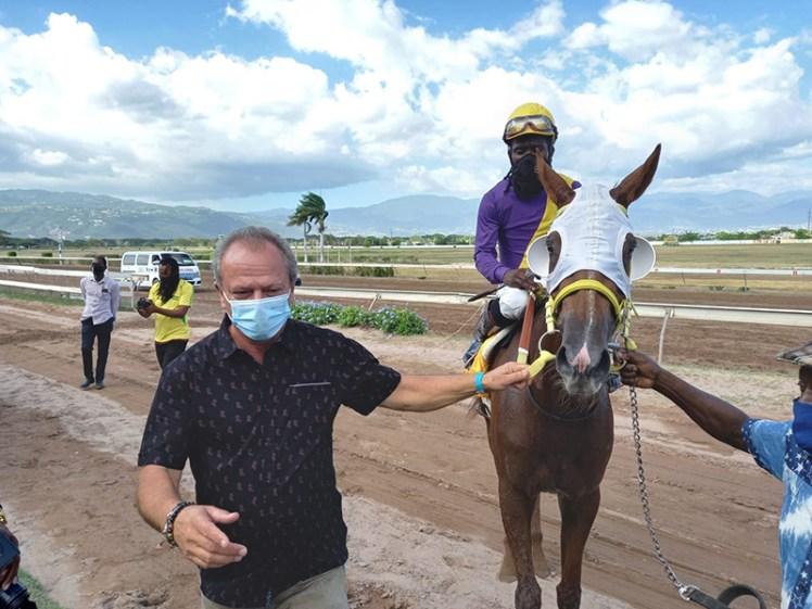 Trainer Gary Subratie leads in Tequila Blue. The jockey is Robert Halledeen)