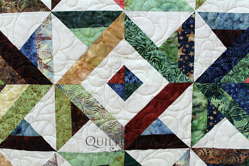 Judy brought me this beautiful quilt with pinwheel blocks and concentric squares made of beautiful batik fabrics. This was calling for a lovely pantograph with lots of movement.