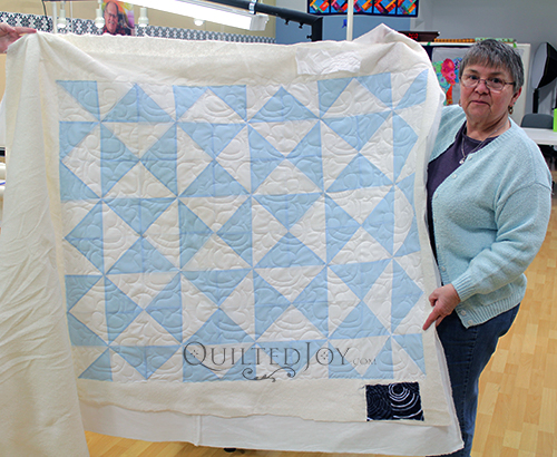 Donna quilted her Quarter Square Triangle quilt on an APQS longarm machine at Quilted Joy
