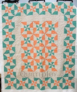 Vintage inspired pinwheel block variation quilt in cream, green, and orange colors