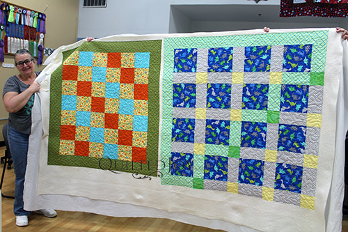 Trina shows off two baby quilts after renting a longarm machine at Quilted Joy