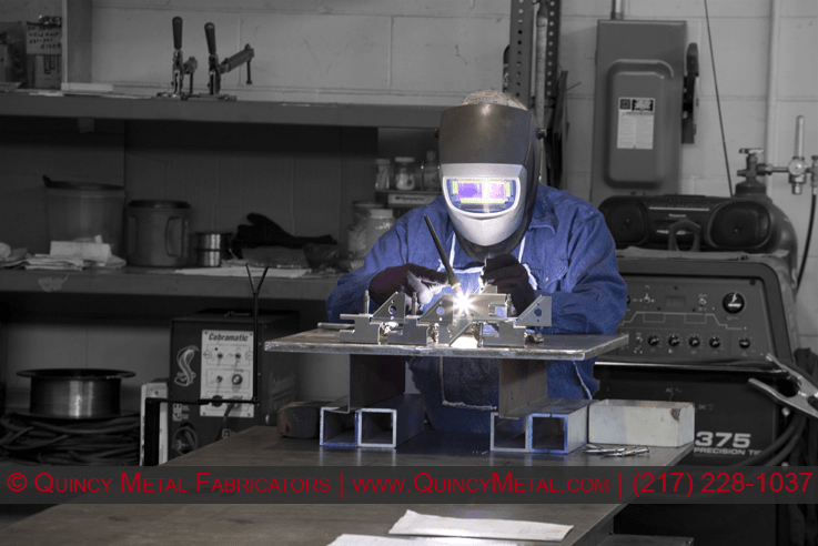 A photo of a welder in Quincy Metal Fabricators' welding department.