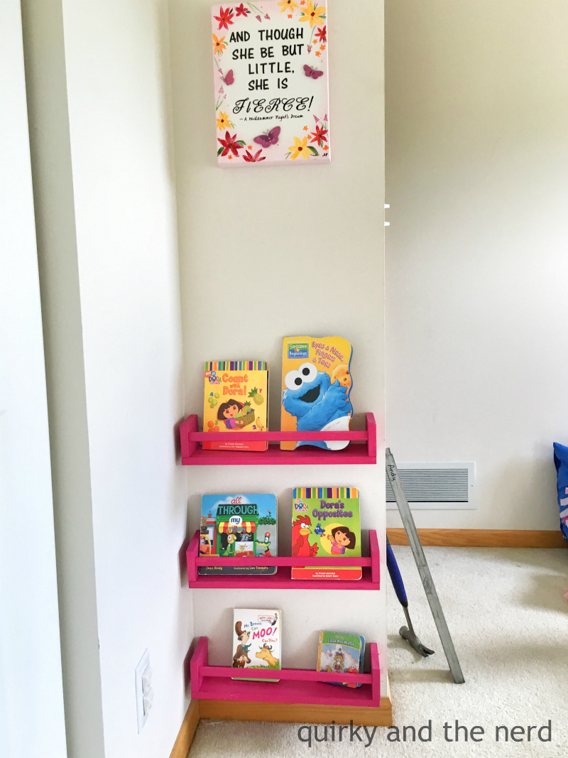 there is a little tiny wall that was just perfect for these book shelves i put some of my least favorite of her books on there because she is teething
