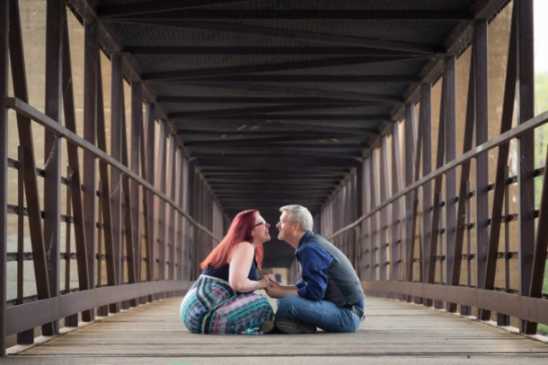 engagement photo session on a bridge, sitting indian style kissing