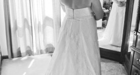 Black and white bridal photo in front of a tri-fold mirror in bride's bedroom