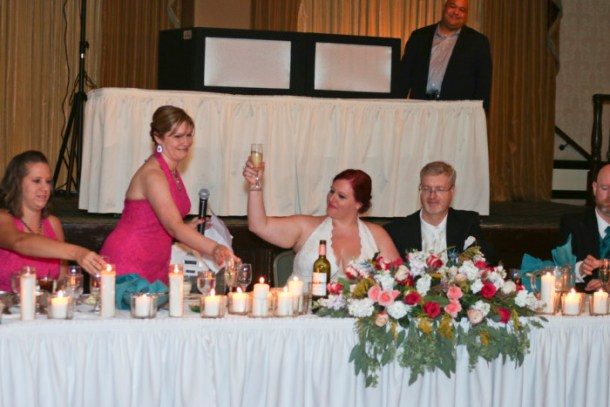raising a glass at the head table at our wedding
