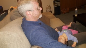 Baby laying in her uncle's lap