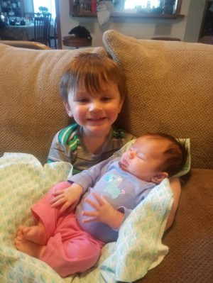 Toddler holding his baby cousin