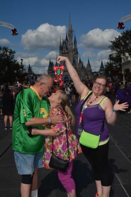 Parents kissing under mistletoe magic shots Disney World